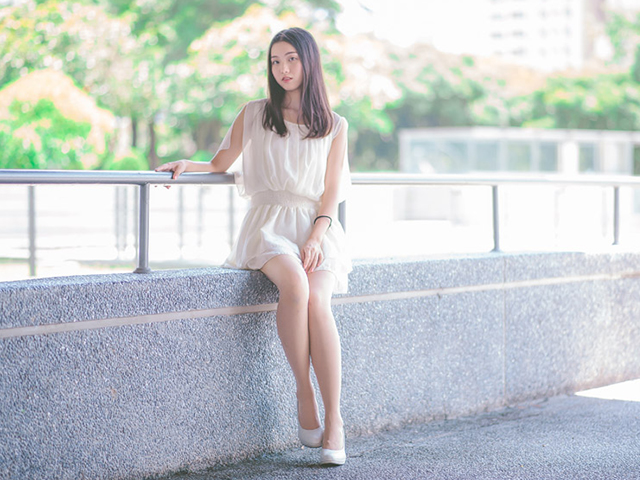 白いワンピース風の服を着てコンクリートの低い壁の上に座っている女性