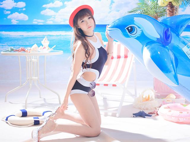 大きなイルカ型うきわと遊ぶ謎の水着を着た女の人