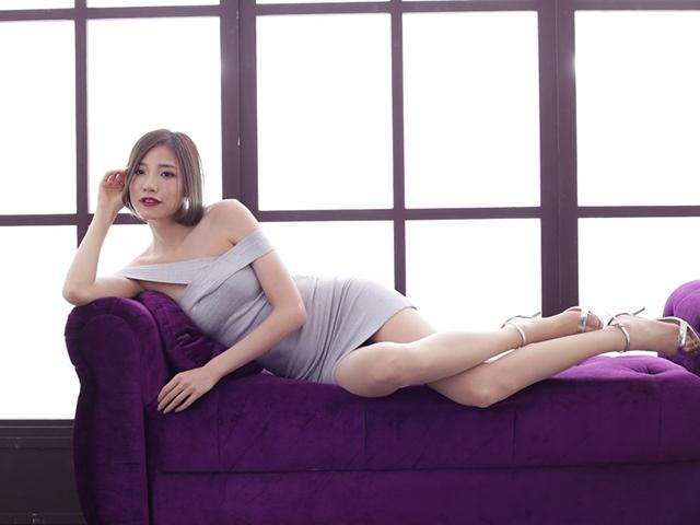 紫のソファーの上で横たわりカメラを見つめ笑みを浮かべる白いドレスの女性