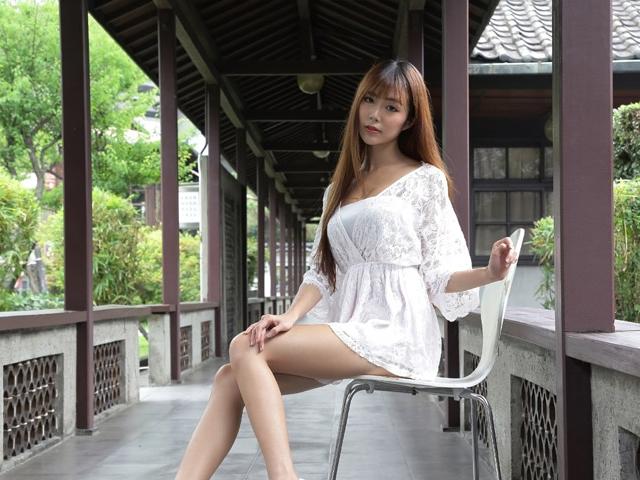 浮いているように見えるほど浅く椅子に腰掛けてこちらを見つめる女性