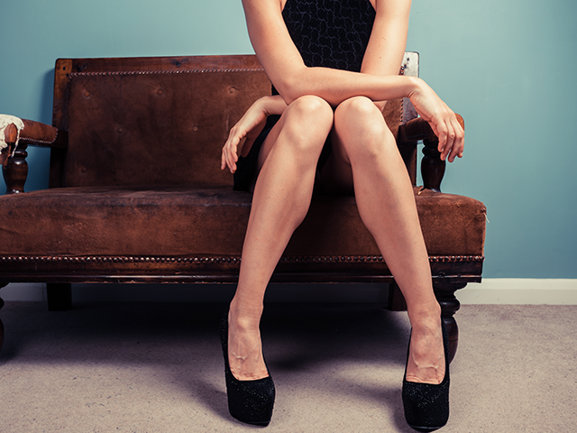 革のソファに座っている女性