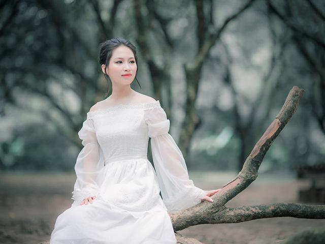 大きな樹の枝の上に腰掛ける白いドレスを着た女の人