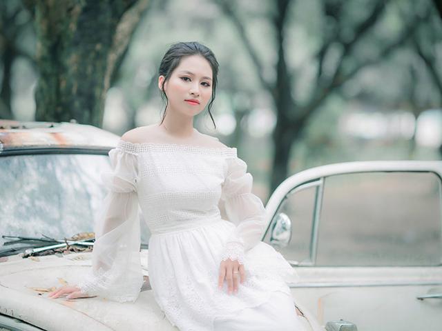 廃車のボンネットの上に座りドヤ顔をするドレス姿の女性