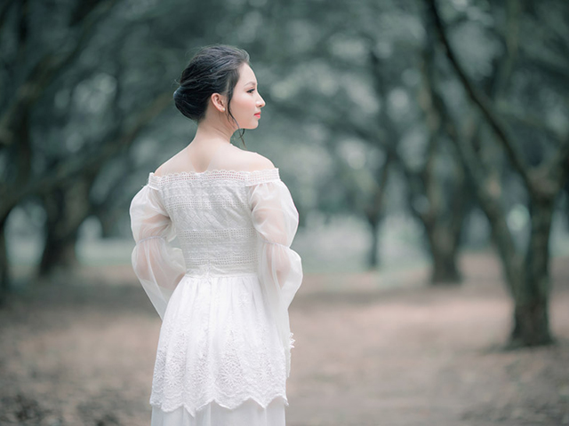 森の奥へと歩みを進める、魔法使いのような雰囲気の白いドレス姿の女性