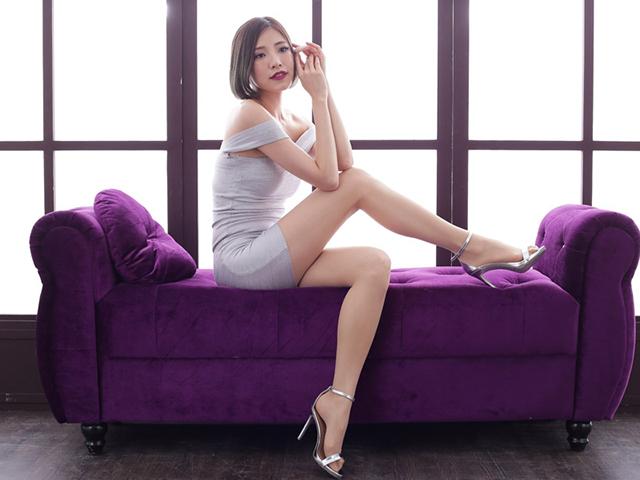 紫のソファに腰掛け、インド神の彫像のようなポーズをしている白いドレスの女性