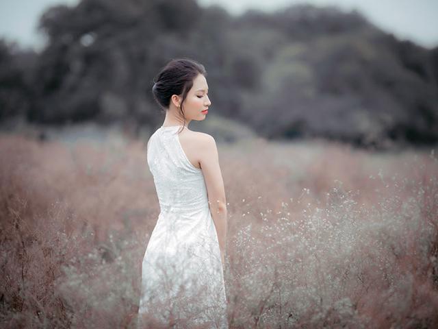 茶色く枯れた草原の中を歩く女の人