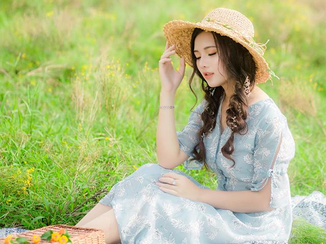 草原の中に座りながら何かを歌う、麦わら帽子を被り水色のワンピースを着た女性