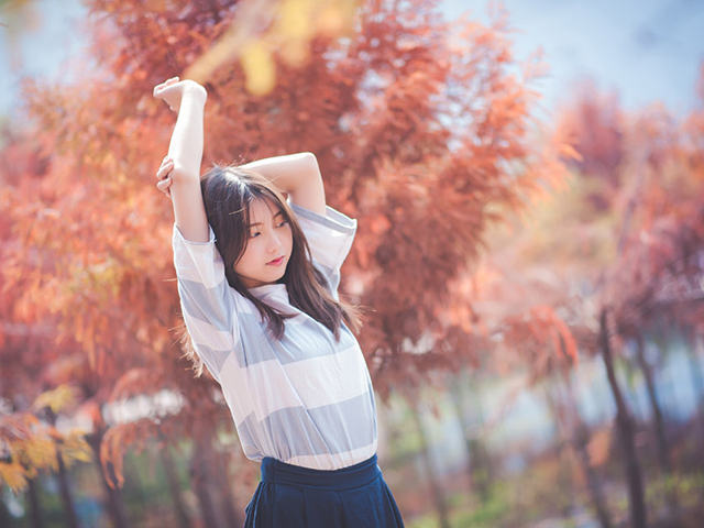 紅葉の中伸びをするどこか昭和を感じさせる女性