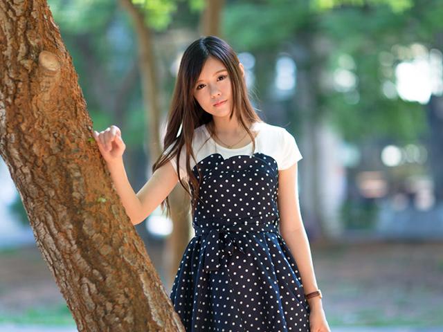 木に片手を当てて身体を支えながら立つ、黒字に白ドットのワンピースを着た女性