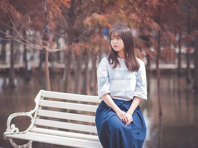 ベンチの手すりに座りどこかを見つめる昭和テイストの女性