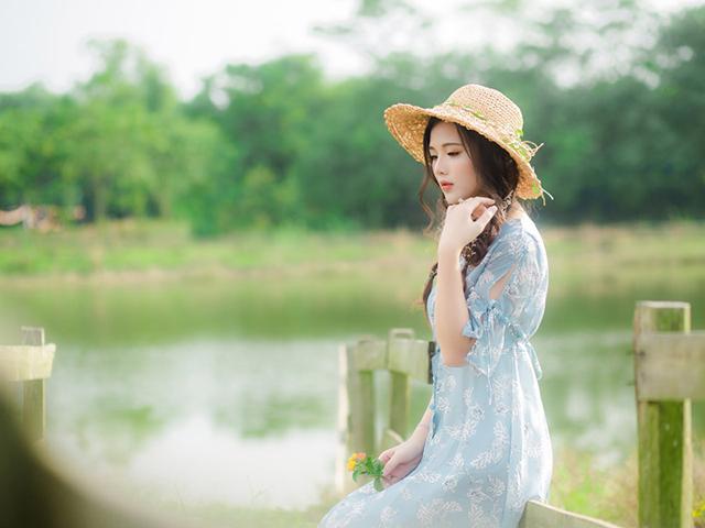 花を一輪手に持ったまま、木でできたフェンスに座っている水色のワンピースを着た女の人