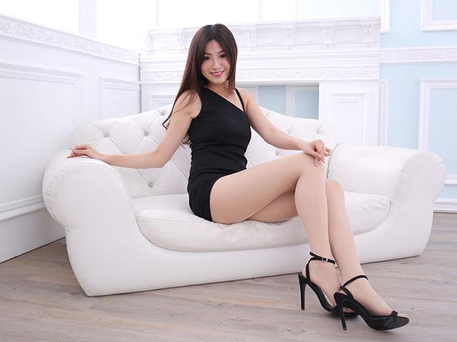 腰を捻り座ったまま笑みを浮かべる黒いドレスの女性