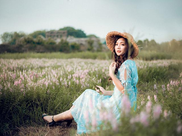 花畑の中に座り込み、こちらを見ている女の人
