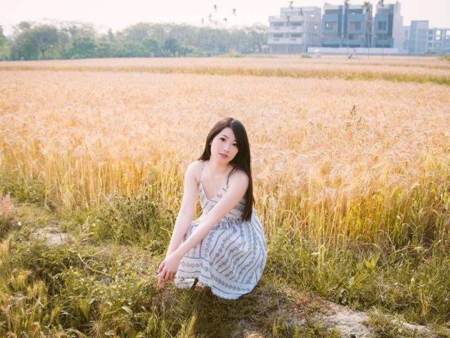 茅の植わる草原にしゃがむ肌の白い女性