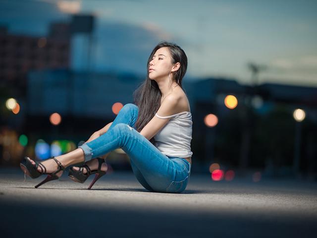 スポットライトの当たる場所で座りながらどこかを見ている女の人