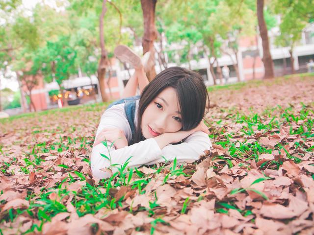 枯れ葉の上で伏臥位になりこちらを見る女性