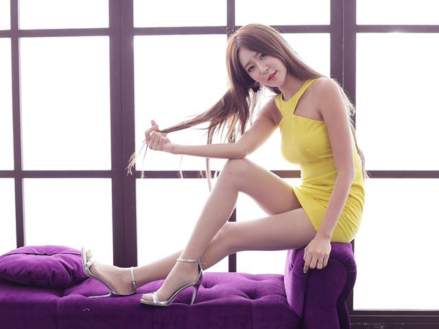 ソファーの手すりに座り座面に足をおいたままこちらを見る黄色いドレスの女性