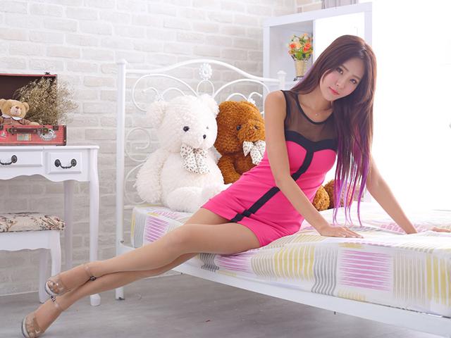 寄り添うくまのぬいぐるみをバックにソファーの上に座りカメラを見つめるピンクのドレスを着た女性