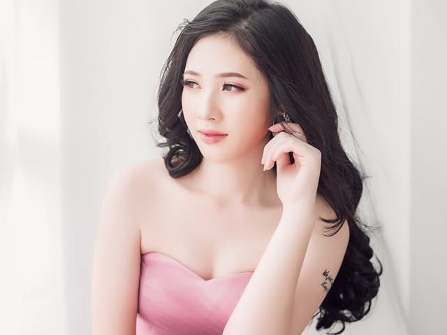 光の消えた目でどこかを見つめる、腕にタトゥーの入ったピンクドレスの女性