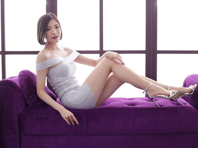 紫のソファーに腰掛け、腰をひねり足を強調させている白ドレスの女性