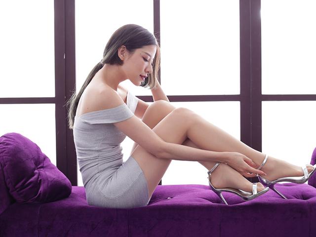 ソファーに腰掛け座面に足を置き、つま先を見つめながら物思いにふける女性