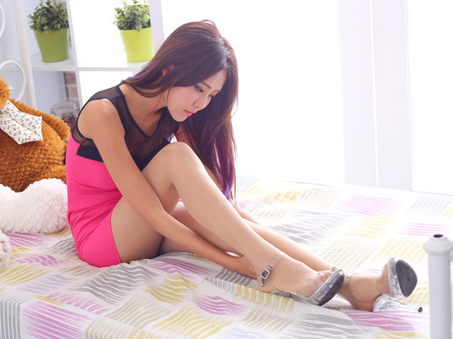 ベッドに腰掛けウィンクをしながら足を見つめる女性