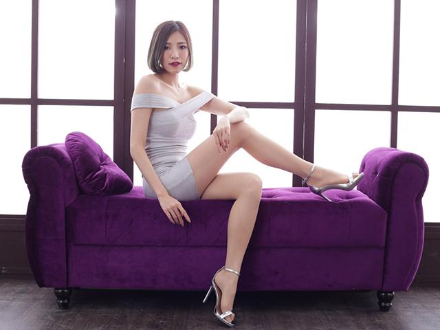 ソファに座り足をアピールしながら見つめてくる女性