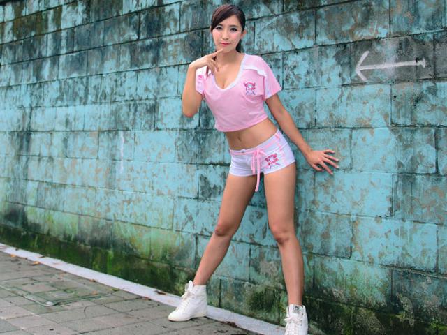 壁の矢印を追って目線を向けるとその先にいる、白のホットパンツとピンクのシャツを着た女性