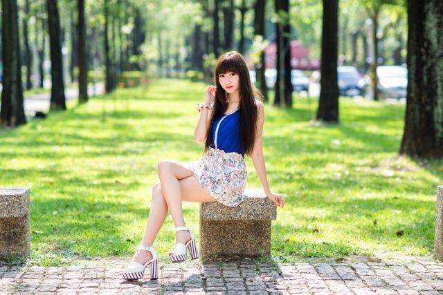 足を組んで石のベンチに座る女性