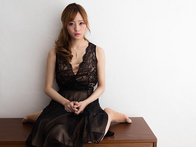 黒いワンピースを着て机に座っている女性