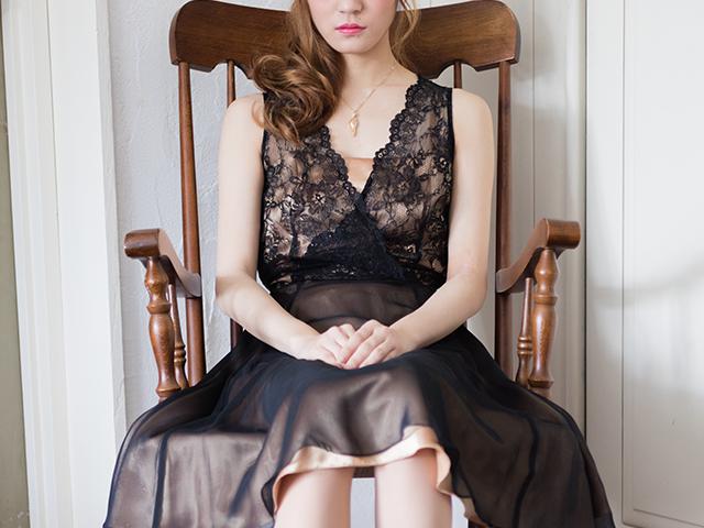 黒いワンピースを着て椅子に座っている女性