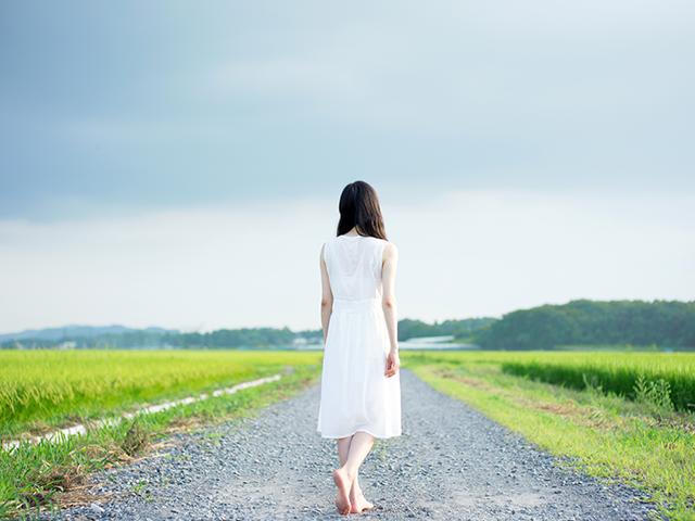 一本道を歩いていく女性