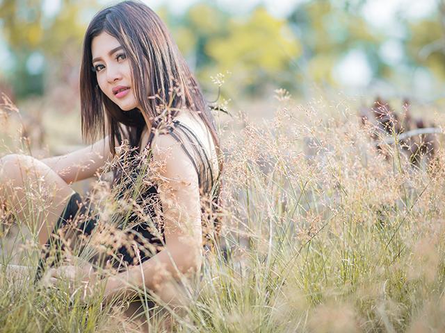 草原の中座り込む女性
