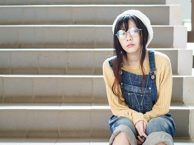 メガネをかけて階段に座っている女性