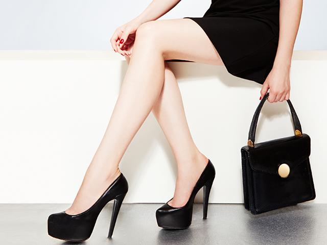 黒ワンピースを着て黒いハンドバッグを持っている女性