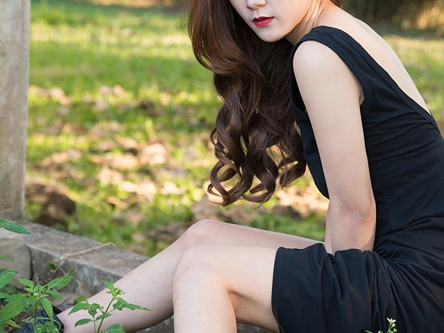 黒いワンピースを着てブロックの上に座っている女性