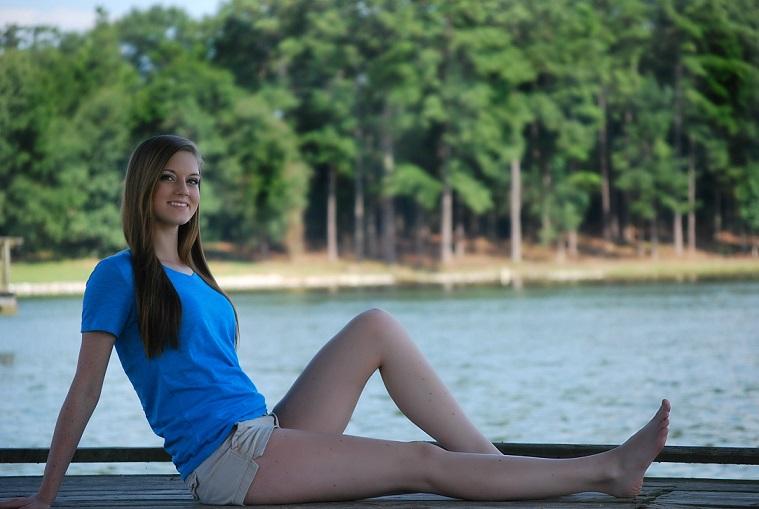 水辺に座る青い服の女性