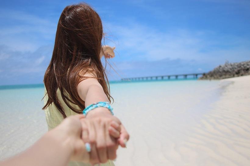 海辺で手を引く女性