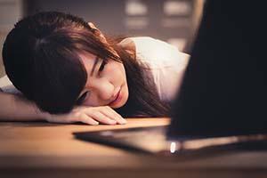 机に寝そべる女性