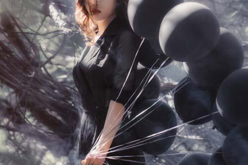 黒い風船を持った女性