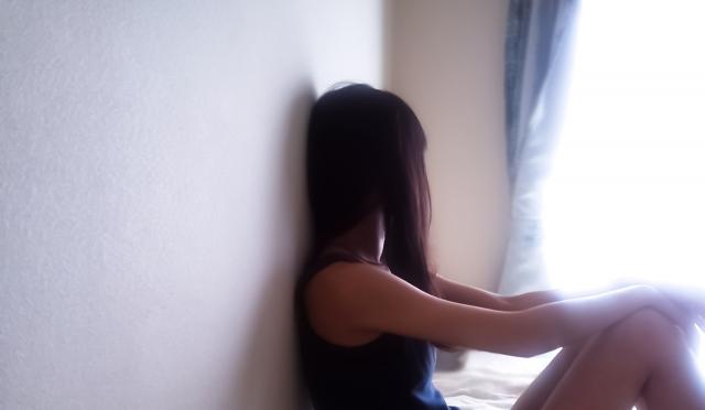 壁にもたれる女の子