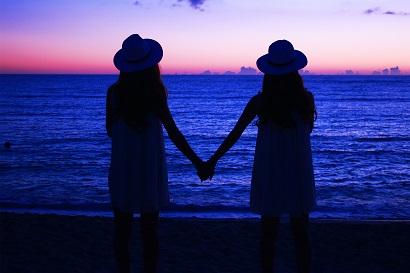 海岸で手を繋ぐ女の子