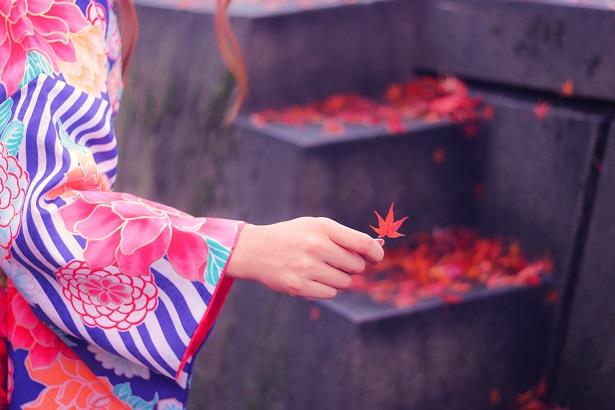 紅葉を摘まんだ女の子