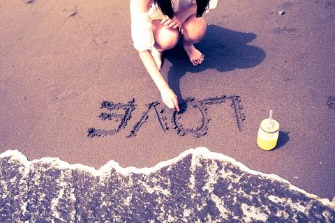 砂浜に文字を書く女の子
